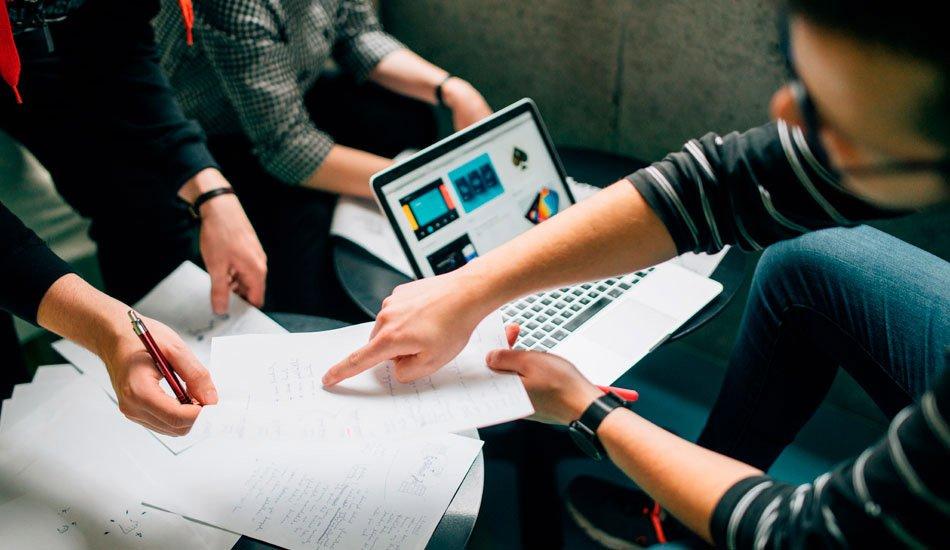 Equipe checando pelo computador os resultados do serviço da agência digital